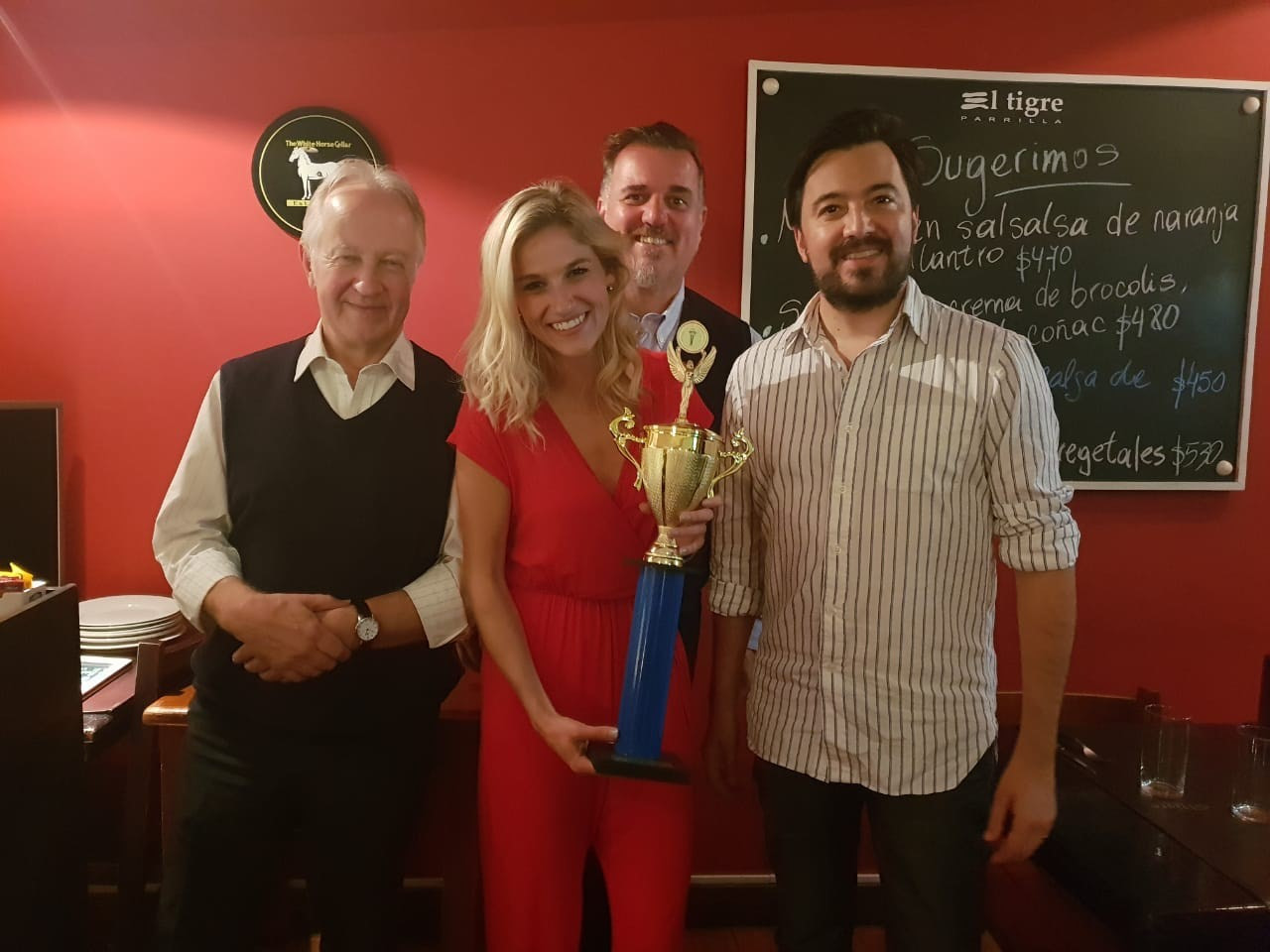 Erin Fish (in red), with her first place trophy for winning the AIPS Young Reporters Program contest (Photo provided by Erin Fish)