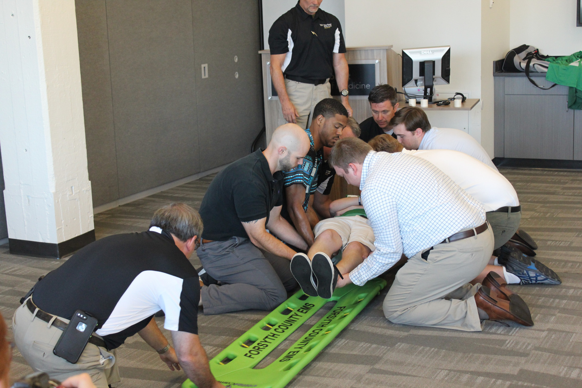 Wake Forest athletic trainer Chris Ina (kneeling, top of spine board) and EMT Jeff Hinshaw (kneeling, bottom of spine board) demonstrate proper technique to placing a spine board under an athlete with a potential spine injury (Daniel Coston Photo)