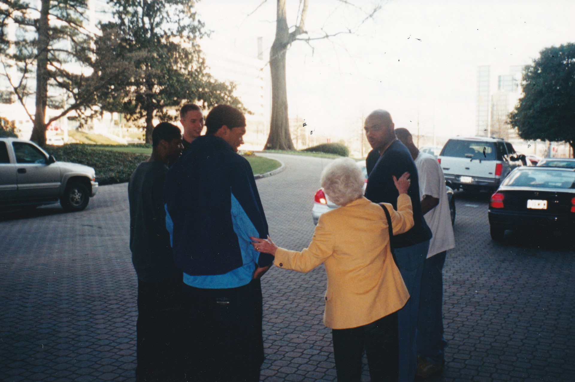 Ann Spencer (yellow jacket, back to camera) talks to a group of University of North Carolina basketball players, along with tv analyst Charles Barkley (second from right)